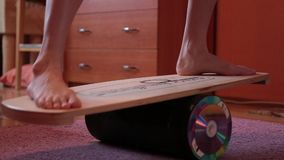 妇女设法保持在委员会的平衡 在平衡板的腿 股票视频