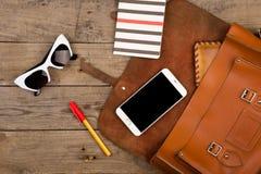 妇女设置了与袋子、巧妙的电话、太阳镜、笔记薄、笔和钱包在棕色木书桌上 免版税库存照片