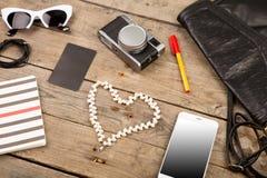 妇女设置了与袋子、巧妙的电话、太阳镜、笔记薄、耳机、照相机、珍珠和标记在棕色木书桌上 免版税库存照片