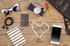 妇女设置了与袋子、巧妙的电话、太阳镜、笔记薄、耳机、照相机、peart和标记在棕色木书桌上 免版税库存照片