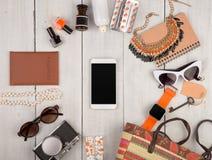 妇女设置了与辅助部件,智能手机,巧妙的手表,护照,照相机,钥匙,笔记本,太阳镜,耳机,化妆用品构成和 库存图片