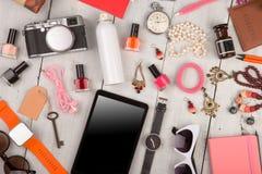 妇女设置了与辅助部件,片剂个人计算机,巧妙的手表,护照,照相机,钥匙,笔记本,太阳镜,耳机,化妆用品构成和 图库摄影