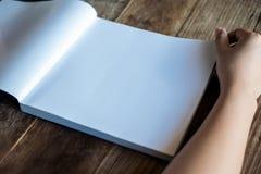 妇女读书和开头在葡萄酒木桌上的一本白色空白的书 库存照片