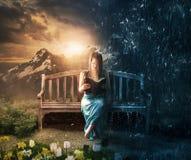 妇女读书在太阳或雨中 免版税库存照片