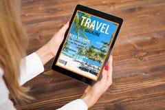 妇女读书在片剂的旅行杂志 库存照片
