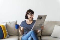 妇女读书报纸和有热的饮料 免版税库存照片