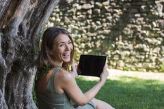 妇女读书片剂和享受休息在公园在树下 免版税库存图片