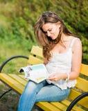 妇女读了一本杂志 库存图片