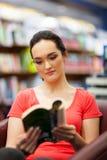 妇女读取在图书馆里 免版税库存图片
