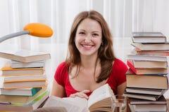 妇女读取她的学校的书。 免版税库存照片
