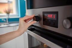 妇女调控烤箱的温度 免版税库存图片