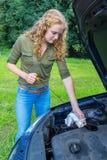 妇女调查汽车与量油计的油面 图库摄影