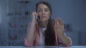 妇女谈的电话和看通过多雨窗口,等待的丈夫在晚上 影视素材