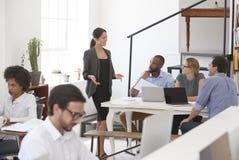 妇女谈话与同事在一张书桌在开放学制办事处 免版税库存图片