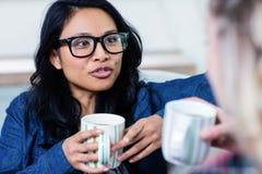 妇女谈话与女性朋友,当在家时喝咖啡 免版税库存图片