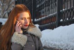妇女谈话与机动性在冬天 免版税图库摄影
