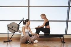 妇女谈话在健身俱乐部的划船器 库存图片