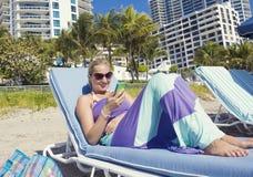 妇女谈话在她的手机,当lounging在海滩时 免版税库存照片