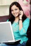 妇女谈话在手机和与膝上型计算机一起使用 库存照片