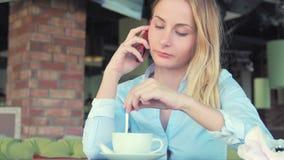 妇女谈话在手机和饮用的咖啡馆拿铁在咖啡馆 股票视频