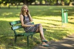 妇女谈话在手机坐一条长凳在公园 免版税库存照片
