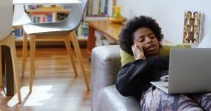 妇女谈话在手机,当使用在沙发在家4k时的膝上型计算机 影视素材