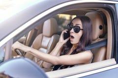 妇女谈话在智能手机,当驾驶汽车时 库存照片