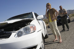 妇女谈话在有交通警文字票的手机在街道上 库存图片