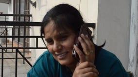 妇女谈话在有他的朋友的智能手机 股票录像