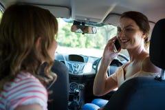 妇女谈话在汽车的手机 免版税库存图片