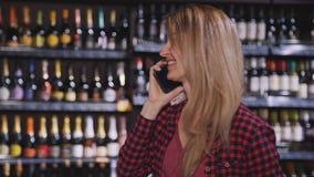 妇女谈话在现代智能手机在超级市场在附近 股票视频