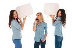妇女谈话在电话和她的拿着讲话泡影的朋友 免版税库存图片