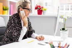 妇女谈话在电话,当与计算机一起使用时 库存图片