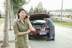 妇女谈话在电话,当技工修理她的汽车时 免版税库存图片
