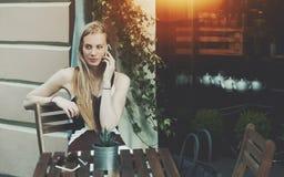 妇女谈话在街道咖啡馆的电话 库存照片