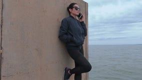 妇女谈话在跳船的电话在海附近 股票录像