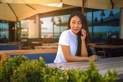 妇女谈话由在城市咖啡馆的电话户外 坐与平板电脑和智能手机的年轻微笑的女孩画象  库存图片