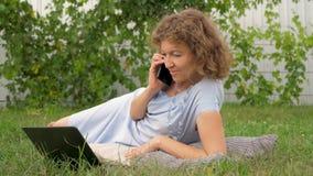 妇女谈话由电话和与笔记本一起使用 股票视频