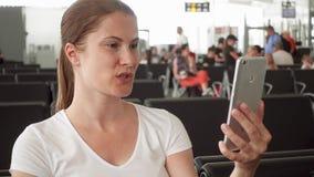 妇女谈话通过智能手机的信使app在机场候诊室,当等待飞行离开时 股票视频