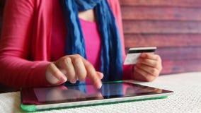 妇女购买和薪水在网上商店在有片剂和信用卡的互联网 股票视频