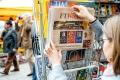 妇女购买新闻FT周末 免版税图库摄影