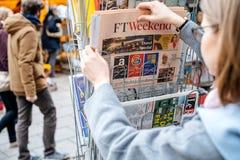 妇女购买新闻FT周末 免版税库存图片