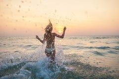 妇女赛跑到有全部的海里飞溅 库存图片