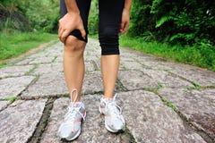 妇女赛跑者受伤的膝盖 库存照片