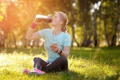妇女赛跑者坐草和饮料新鲜的绿色戒毒所sm 免版税库存照片