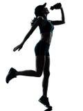 妇女赛跑者慢跑者饮用的剪影 库存照片