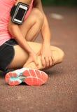 妇女赛跑者持有人她扭转的脚腕 免版税库存图片