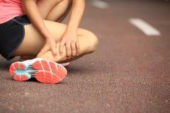 妇女赛跑者持有人她扭转的脚腕 库存照片