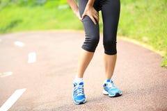 妇女赛跑者持有人她的体育腿受伤 库存照片