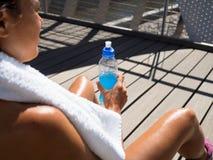 妇女赛跑者有一份精力充沛的饮料在锻炼以后 免版税库存图片